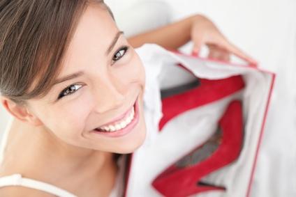 Eine Frau mit einem offenen Karton und roten Pumps