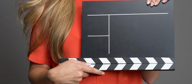 Eine Frau hält eine unbeschriftete Filmklappe