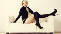Blonde Frau liegt auf dem Sofa
