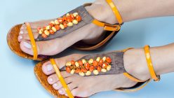 Eine Frau trägt schicke gelb-orange Sandalen