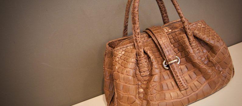 Eine braune Handtasche auf einem creme-farbenen Boden