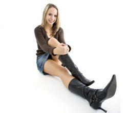 Frau mit Lederstiefeln auf dem Boden stizend