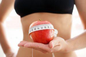 Eine Frau hält einen Apfel, mit einem Maßband darum, in der Hand