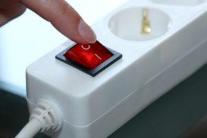 Finger der den Schalter an einer Steckdosenleiste betätigt
