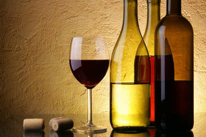 Drei Weinflaschen und ein Weinglas