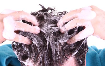 Mann reibt sich mit Shampoo die Haare ein