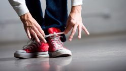 Mann schnürrt sich die Schuhe