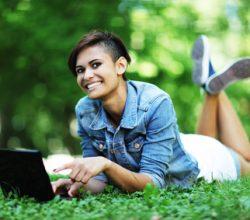 Frau liegt mit Laptop auf einer Wiese