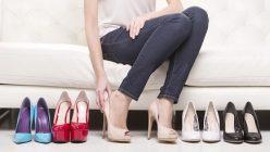 Frau probiert mehrere Paar Schuhe an