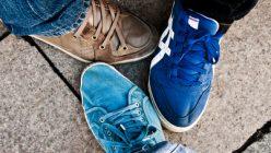 3 Sneakerträger stellen die Füße zusammen