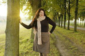 Übergewichtige erwachsene Frau mit langen dunklen Haaren ist herbstlich gekleidet und steht draußen in einer Allee.