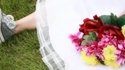 Braut sitzt auf Wiese