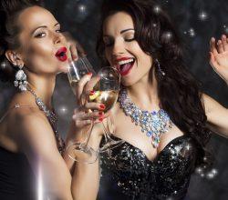 Lachende Frauen trinken Champagner