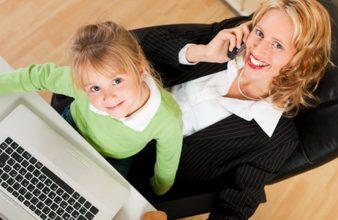 Geschäftsfrau und Mutter arbeitet mit Tochter im Arm im Interne